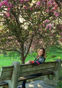 Georgia Sitting on a bench under a cherry tree in bloom