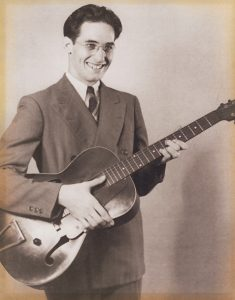 Finnegan standing with guitar